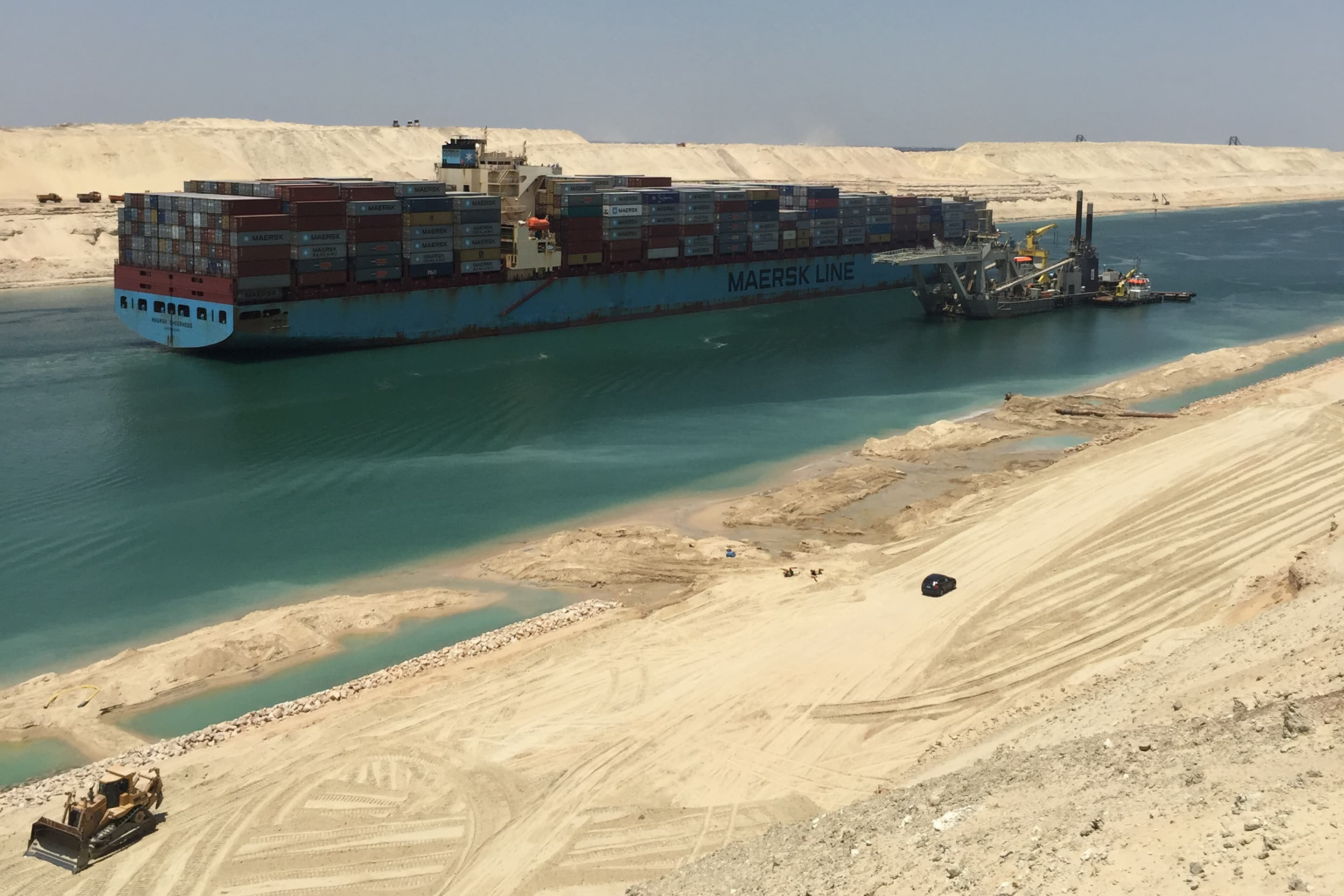 A container vessel passes the dredger Phoenix 1 during a trial run through the parallel canal