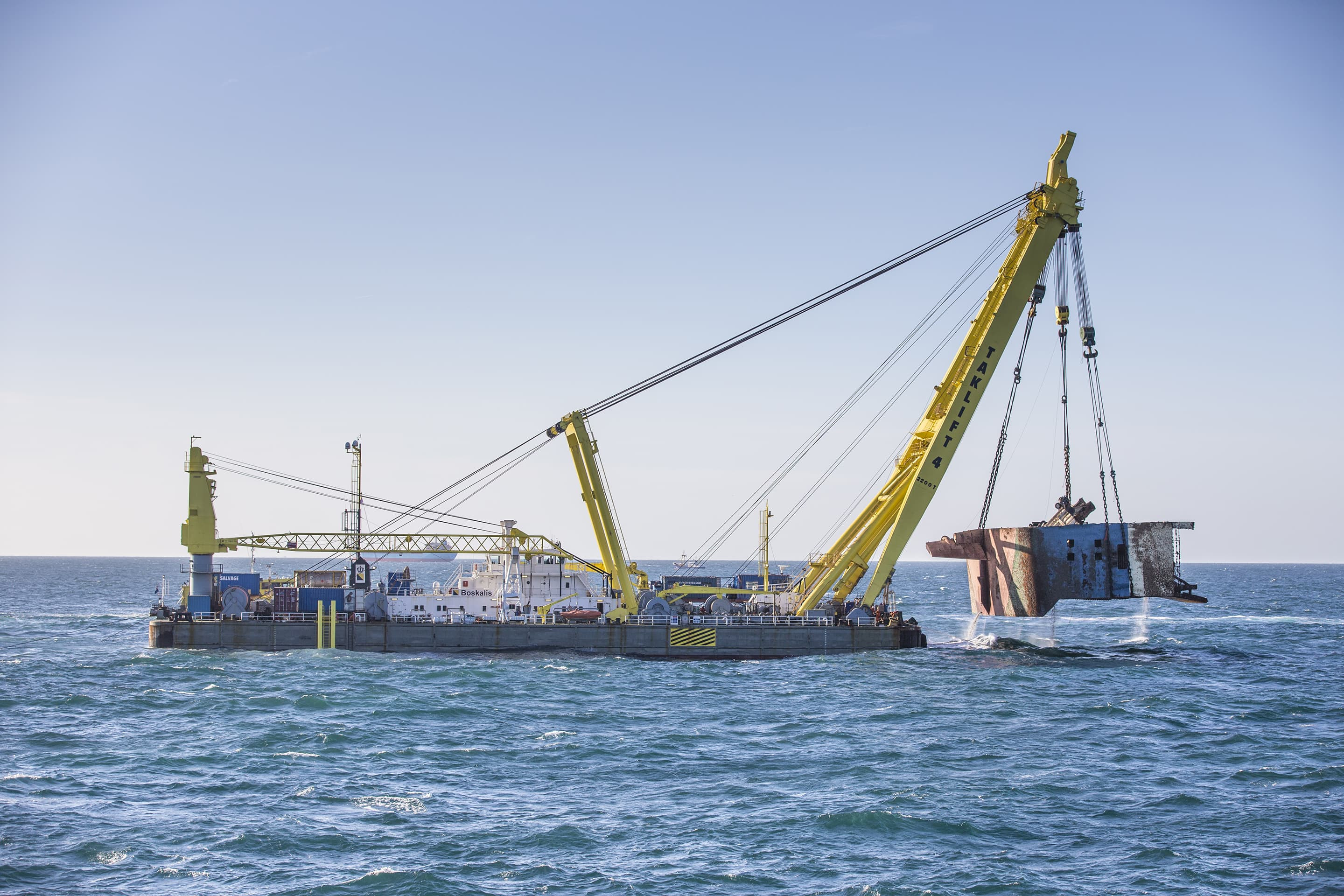 The floating sheerleg Taklift 4 is lifting one of the wreck sections