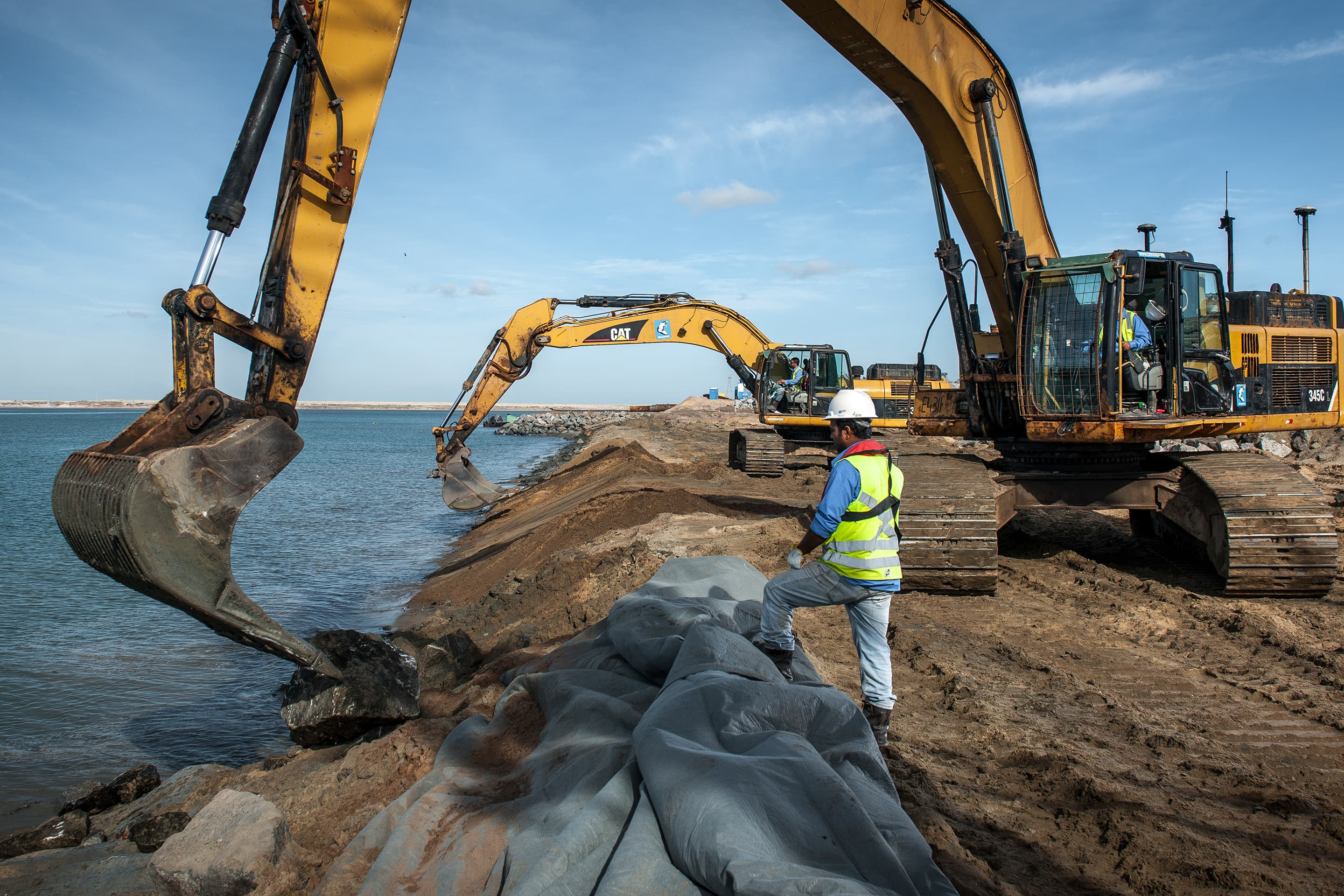 Installation of geotextile to protect a breakwater against erosion
